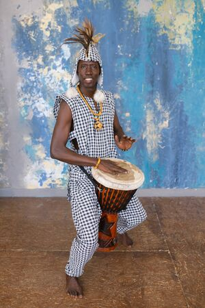 African artist in traditional clothes playing djembe drum 写真素材