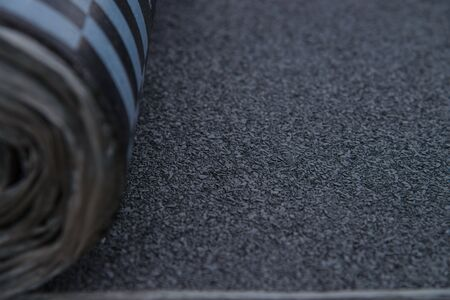 Waterproof bitumen roll covered with insulation materials, abstract background, closeup texture.