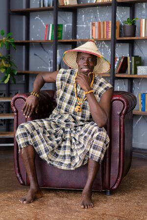 Happy Handsome african man in traditional clothes sitting on chair