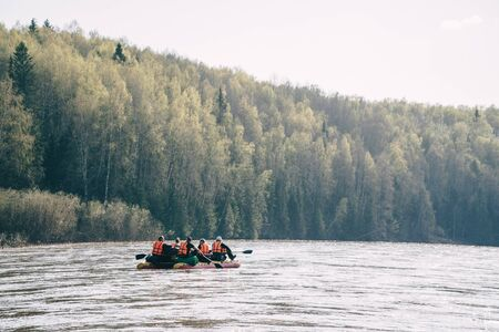 Team of people float down the River on inflatable catamaran. Archivio Fotografico