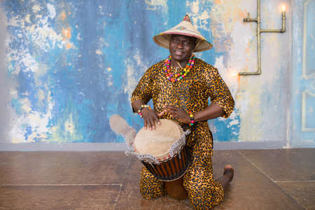 Handsome african drummer weared in traditional costume playing on djembe drum.