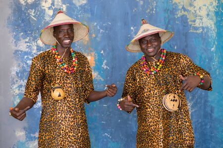 Handsome african men in traditional Fulani hats and colorful clothes smiling and looking at camera.