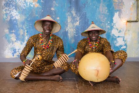 African artist in traditional clothes playing on ethnic musical instruments .