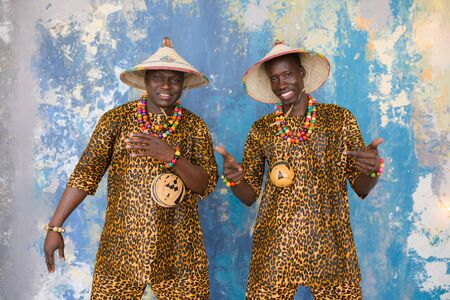 Handsome african men in traditional Fulani hats and colorful posing at studio