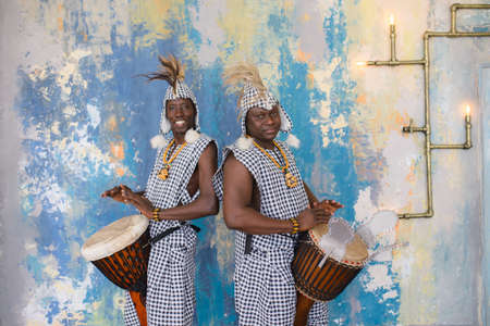 A group of people in traditional african costumes playing jembe drums.