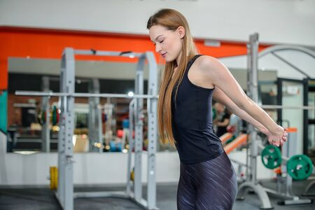 Portrait of fitness woman stretching at gym before workout. Female stretch her chest. Sports activity, healthy lifestyle.