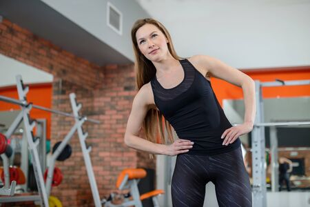 Portrait of fitness woman stretching at gym before workout. Sports activity, healthy lifestyle. Sideways lean exercise.
