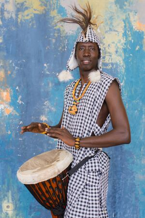 African artist in traditional clothes playing djembe drum Standard-Bild