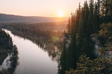 Scenic landscape, man on on edge of cliff meeting beutiful sunrise over mountain river Usva, Russia, Ural mountains