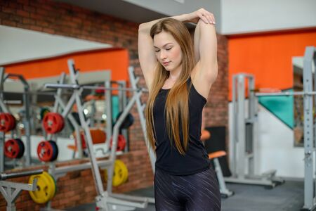 Portrait of fitness woman stretching at gym before workout. Female stretch back of upper arm, triceps. Sports activity, healthy lifestyle.