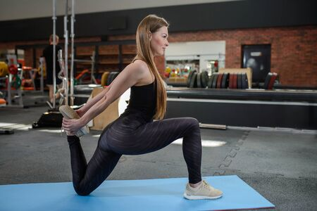 Portrait of fitness woman stretching at gym before workout. Leg stretches. Sports activity, healthy lifestyle.