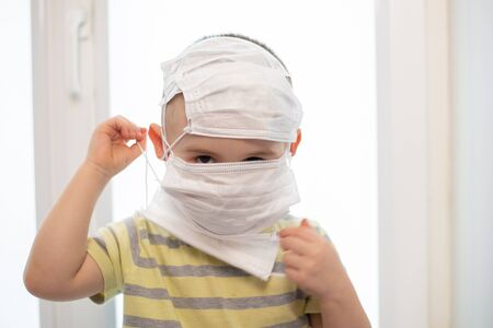 Toddler boy in wearing many medicine masks, quarantine at home, virus protection Standard-Bild