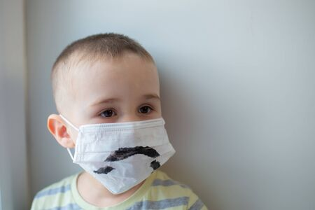 Unhappy boy in medicine mask, closeup portrait, quarantine at home, virus protection