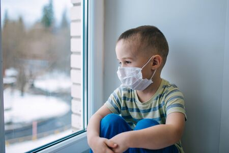 Sad little boy in medicine mask sitting near window and looking outside, quarantine at home, virus protection