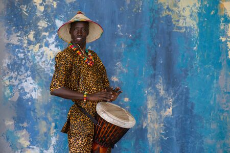 African man in traditional clothes playing djembe drum Standard-Bild