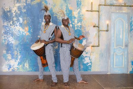A group of people in traditional african costumes playing jembe drums