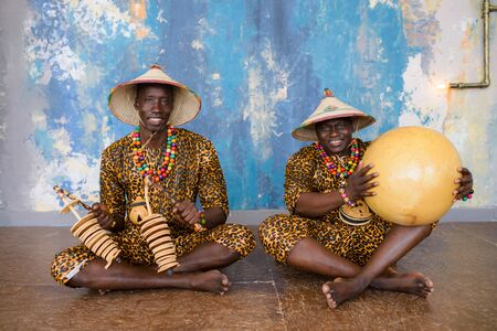 African artist in traditional clothes playing on ethnic musical instruments