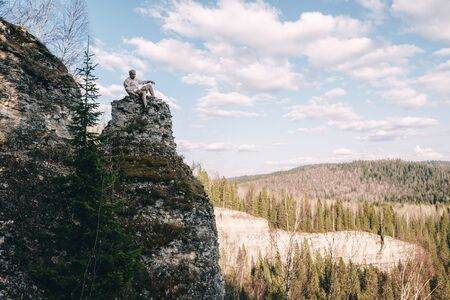 Young hiker looking down from a top of a mountain. Standard-Bild