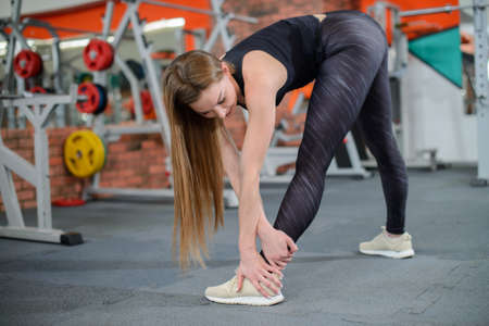 Portrait of fitness woman stretching at gym before workout. Sports activity, healthy lifestyle.