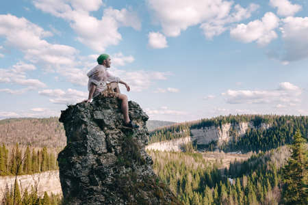 Young hiker sitting and relaxing on top of a mountain.