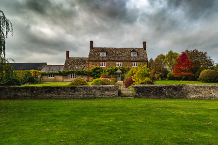 Exterior architecture of beautiful masonry cottage with green lawn and aged fence under gloomy cloudy sky, Oxford, United Kingdom 新聞圖片