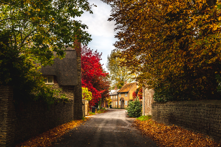 Empty roadway among stone fences of rural stone houses among lush colorful trees in autumn, Oxford, United Kingdom