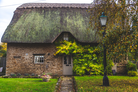 Facade of aged rural cottage with mossy roof and green bushes on front wall, Oxford, United Kingdom