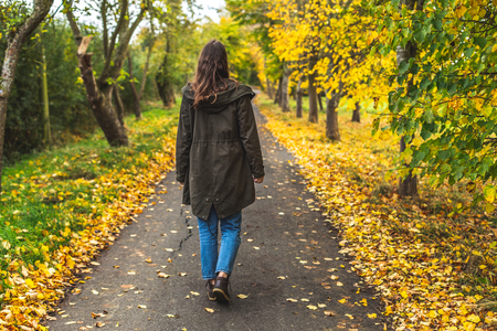 Back view of woman in coat walking in solitude on narrow pathway among colorful autumnal trees in park, Oxford, United Kingdom