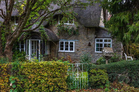Exterior of  old gray stone house with trees and live hedge in autumn time, Oxford, United Kingdom
