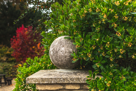 Aged stone ball on gray fence among bright autumnal foliage, Oxford, United Kingdom
