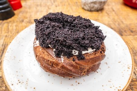 curd ring with poppy seeds on a white plate, top view