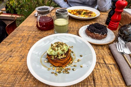 Breakfast in the cafe with sweet potato pancakes, matcha latte, curd ring, cranberry tea and omelette. wooden table.