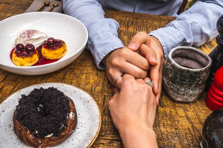 newlyweds hold hands close-up in a cafe Banque d'images