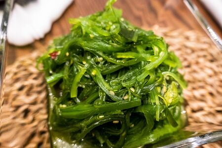 Healthy wakame seaweed salad on wooden board. Top view.