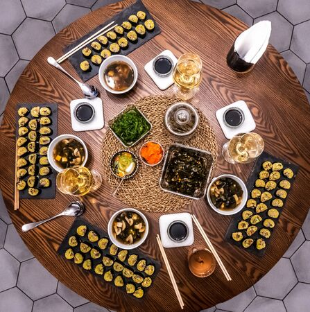 Traditional Japanese food - sushi, rolls and sauce on a wooden table. Top view