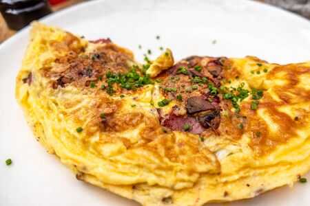 Breakfast food - Omelette with meat, cheese, onion on the white plate