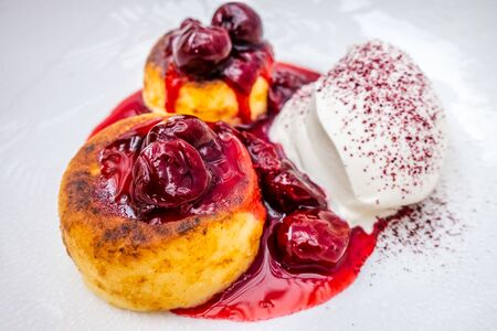 cottage cheese pancakes with sour cream on white plates