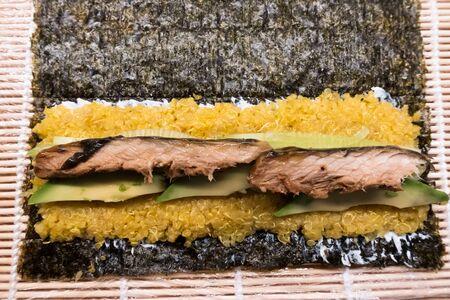 bamboo rolling mat for homemade sushi with nori, ricota, quinos, cucumber and mackerel 免版税图像 - 132154836