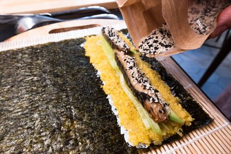 bamboo rolling mat for homemade sushi with nori, ricota, quinoa, cucumber, mackerel sprinkle with sesame seeds Banque d'images
