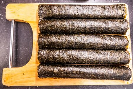 Homemade sushi rolls on cutting board. Five uncut nori rolls