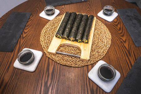 Homemade sushi rolls on cutting board. Five uncut nori rolls and soy sauce served on table