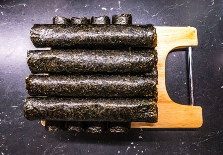 Homemade sushi rolls on cutting board. uncut nori rolls