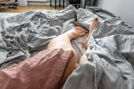 Mens and womens morning legs in bed under a blanket 版權商用圖片