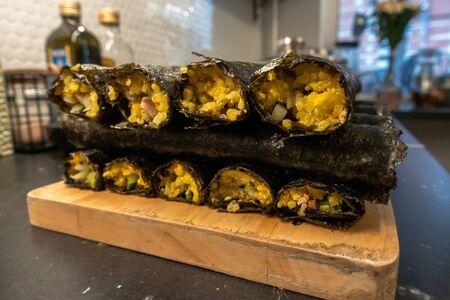 Homemade sushi rolls on cutting board on kitchen 免版税图像