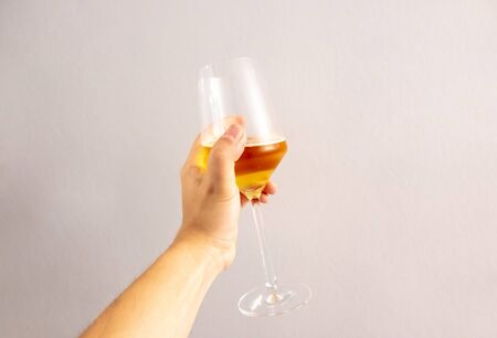 hand with a wine glass with cider against a background