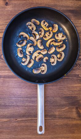 sliced fried mushrooms champignons spread out in a pan on a wooden table