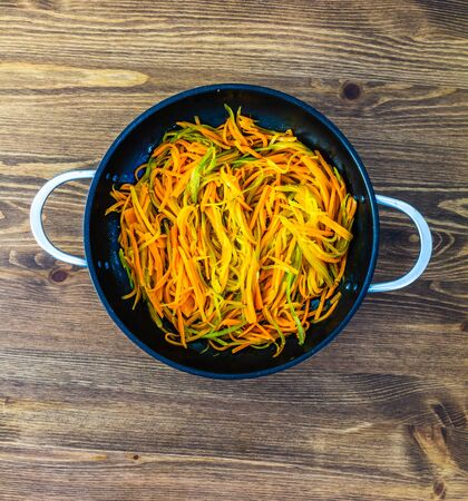 thinly cut thin strips of carrots. fried and stewed carrot spaghetti in a pan on a wooden table 免版税图像 - 132153901