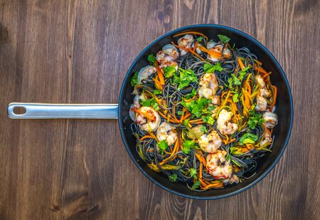 homemade black spaghetti with cuttlefish ink, with shrimp, dill and carrots. in a pan on a wooden table. healthy home dinner Banque d'images