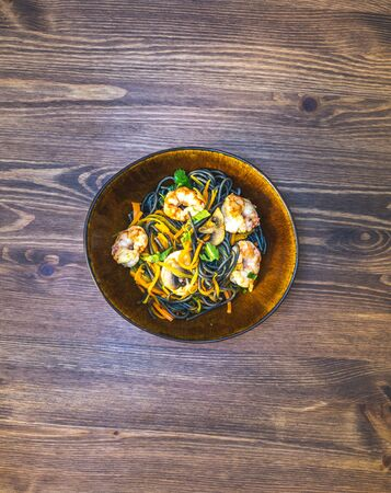 homemade black spaghetti with cuttlefish ink, with shrimp, dill and carrots. in a bowl on a wooden table. healthy home dinner