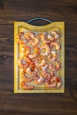 raw frozen prawns laid out on a cutting board on a wooden table